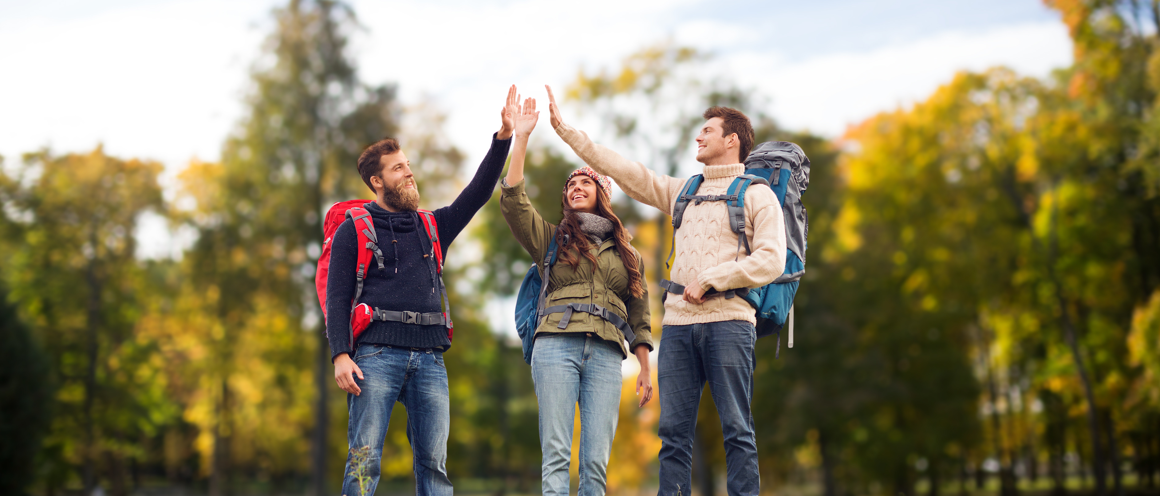 travel, tourism, hike, gesture and people concept - group of smiling friends with backpacks making high five over natural background
