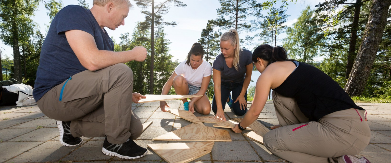 Male and female coworkers solving wooden plank puzzle on patio in forest